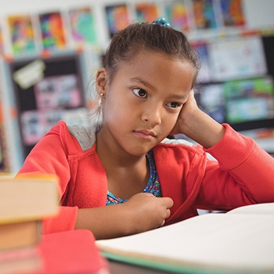 Thoughtful schoolgirl sitting at desk in classroom